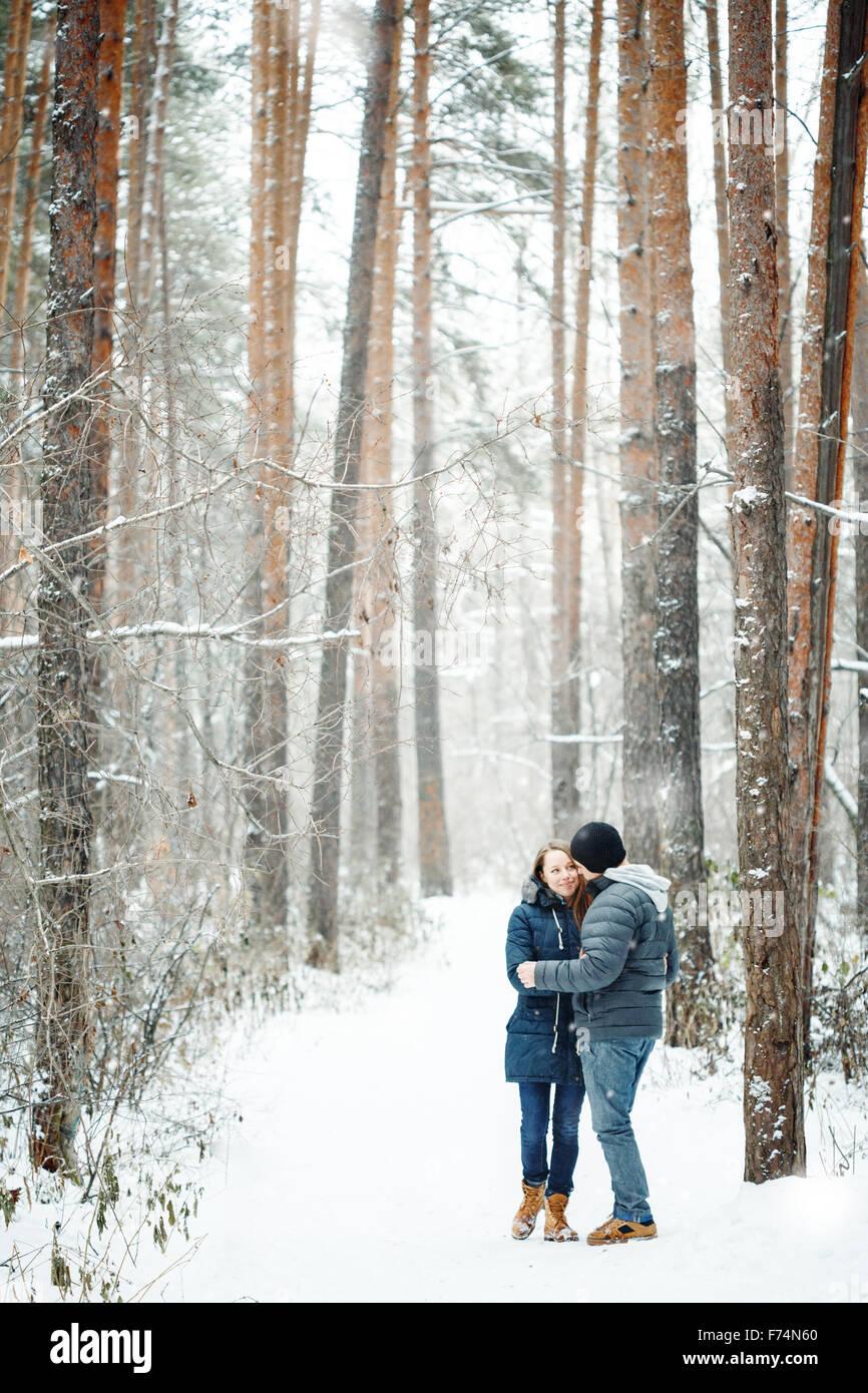 Young Couple Embracing in Winter Forest. Les vacances d'hiver. Week-end d'évasion. L'espace pour le texte. Couleurs Banque D'Images