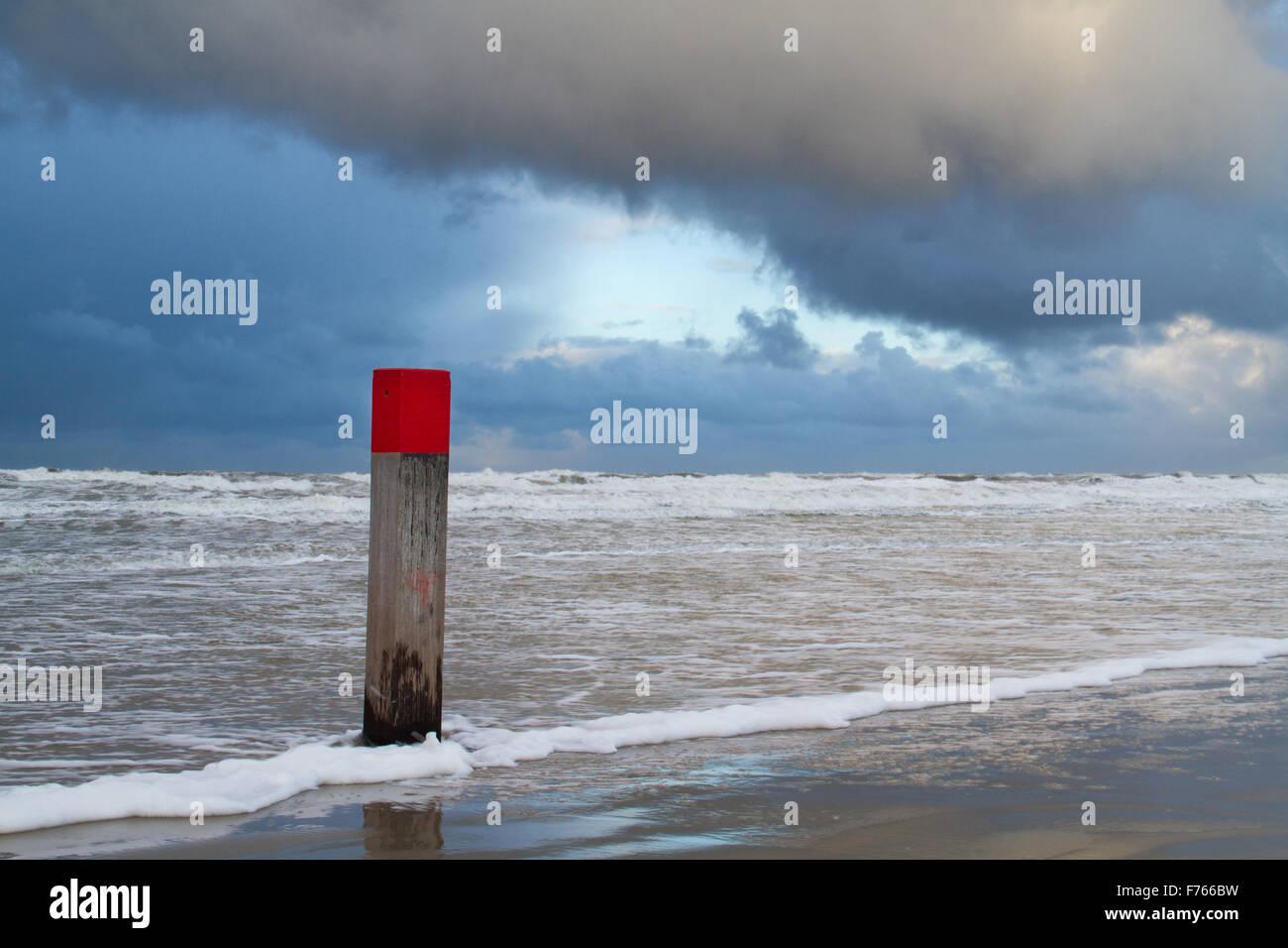 Pôle de plage avec tête rouge à marée haute sous un nuage sombre Photo Stock