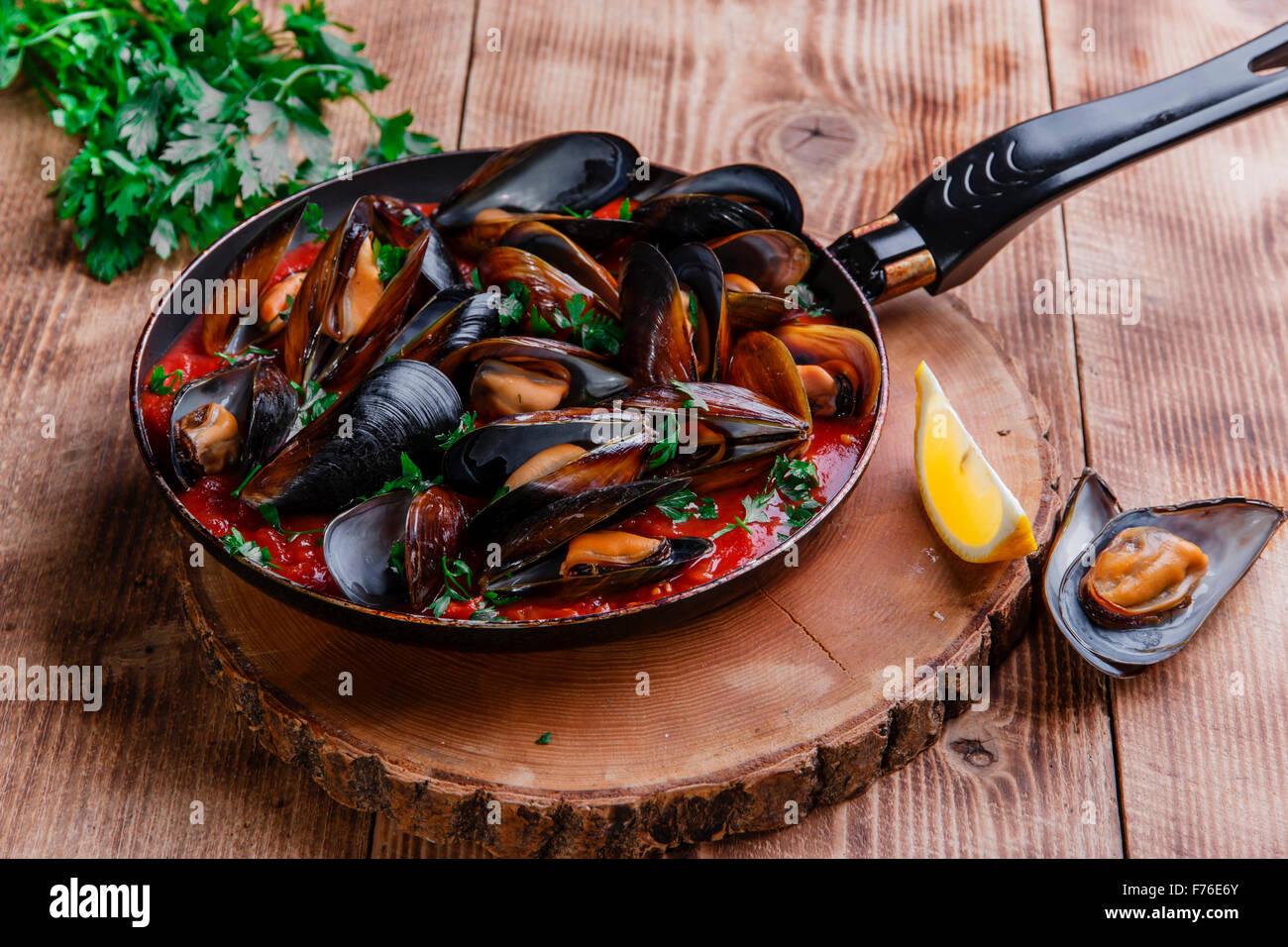 Dans les moules huîtres sauce rouge dans une poêle Banque D'Images