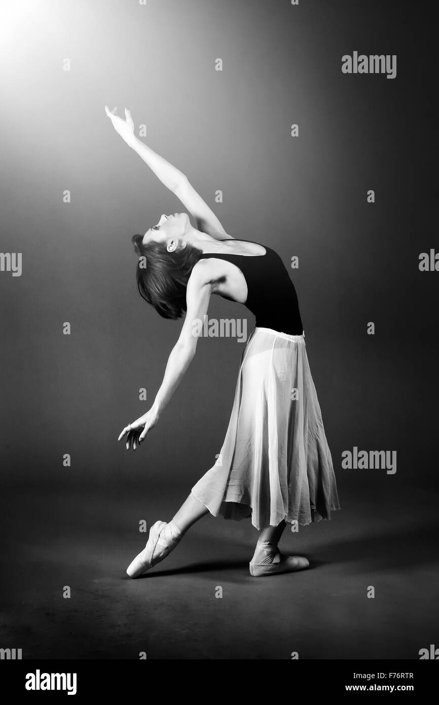 Danseuse de ballet à la recherche dans la lumière en pose gracieuse Photo Stock