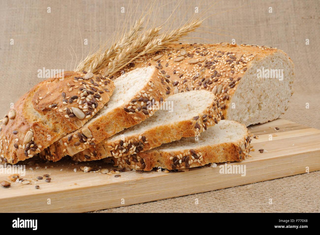 Tranches de pain de grains entiers de céréales sur une planche en bois Photo Stock