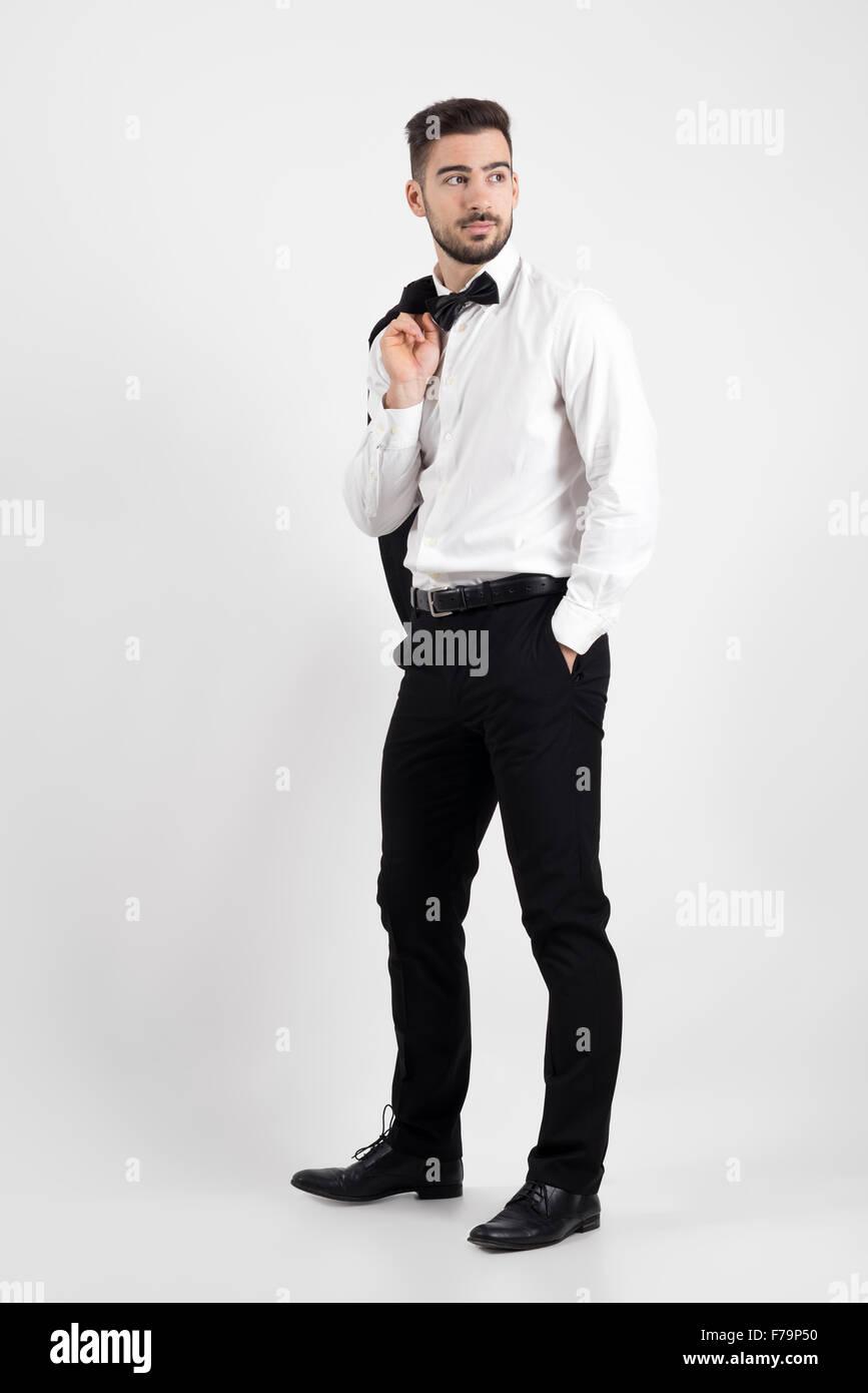 Vue latérale d'homme élégant holding veste de costume par-dessus son épaule à la voiture Photo Stock