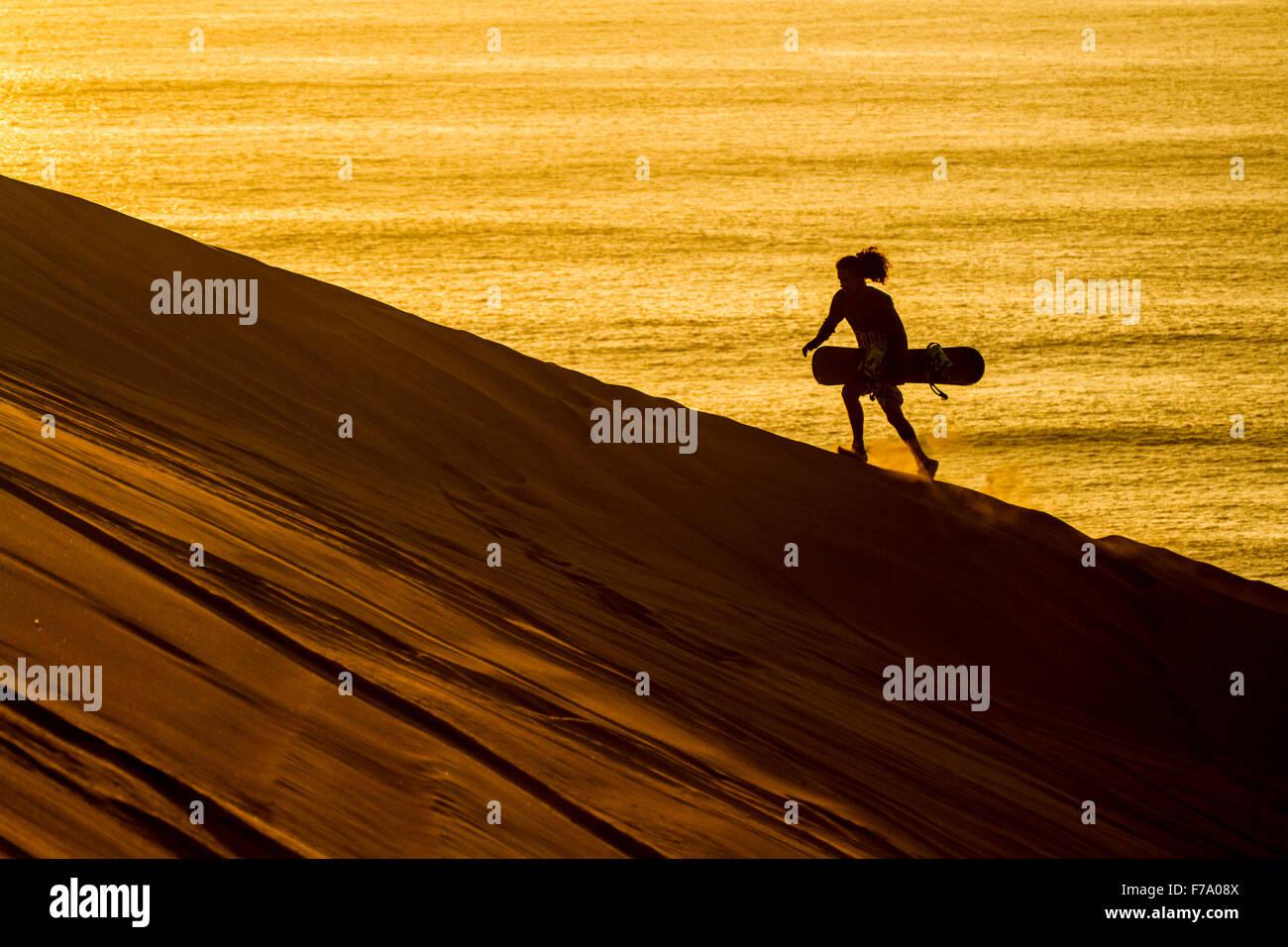 Silhouette d'un sandboarder balade au coucher du soleil à Cerro Dragon, une dune de sable situé à Photo Stock