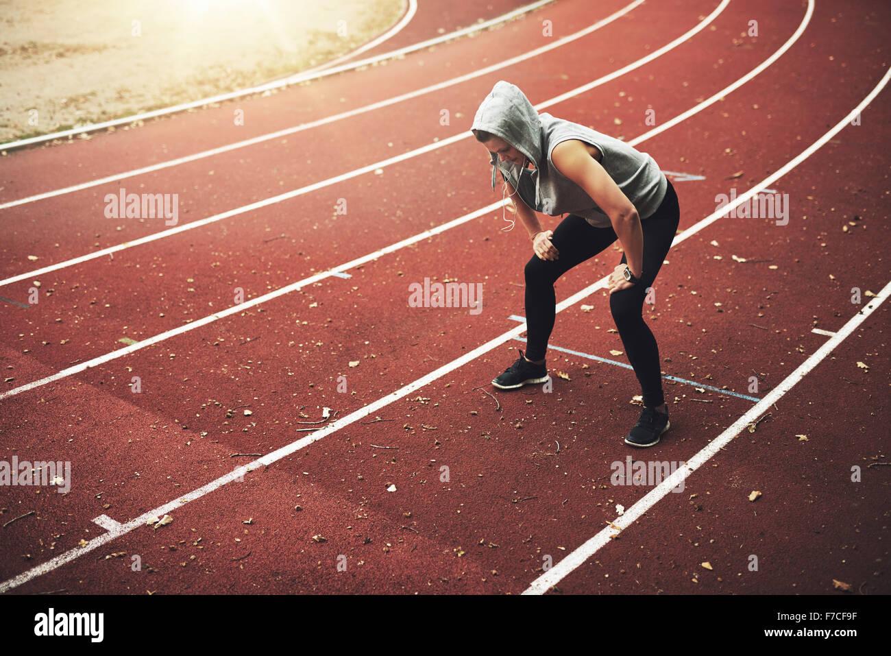 Jeune coureuse debout sur le stade et l'écoute de la musique, se détendre après l'exécution Photo Stock