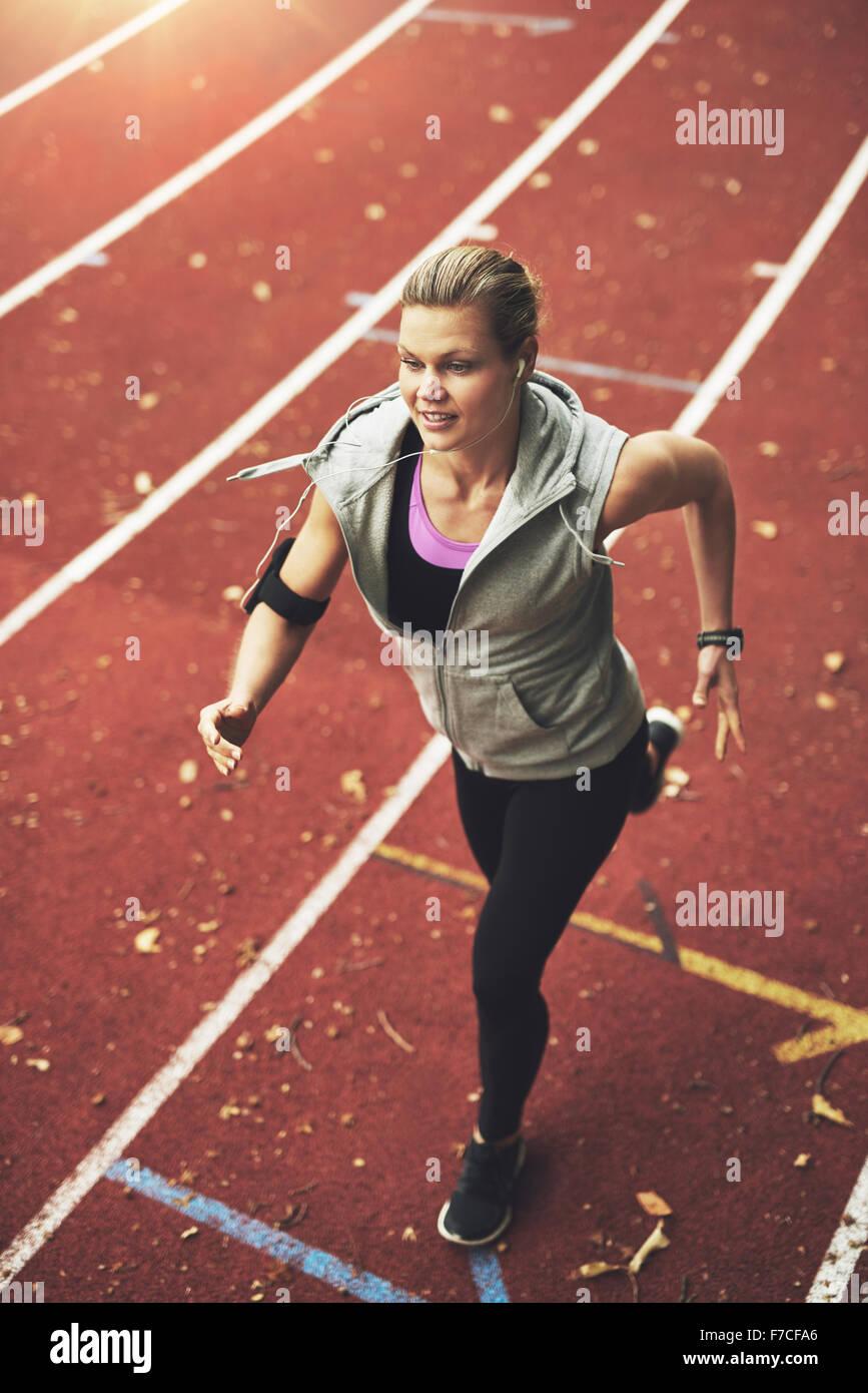FIt young woman running sur piste tout en écoutant de la musique Photo Stock