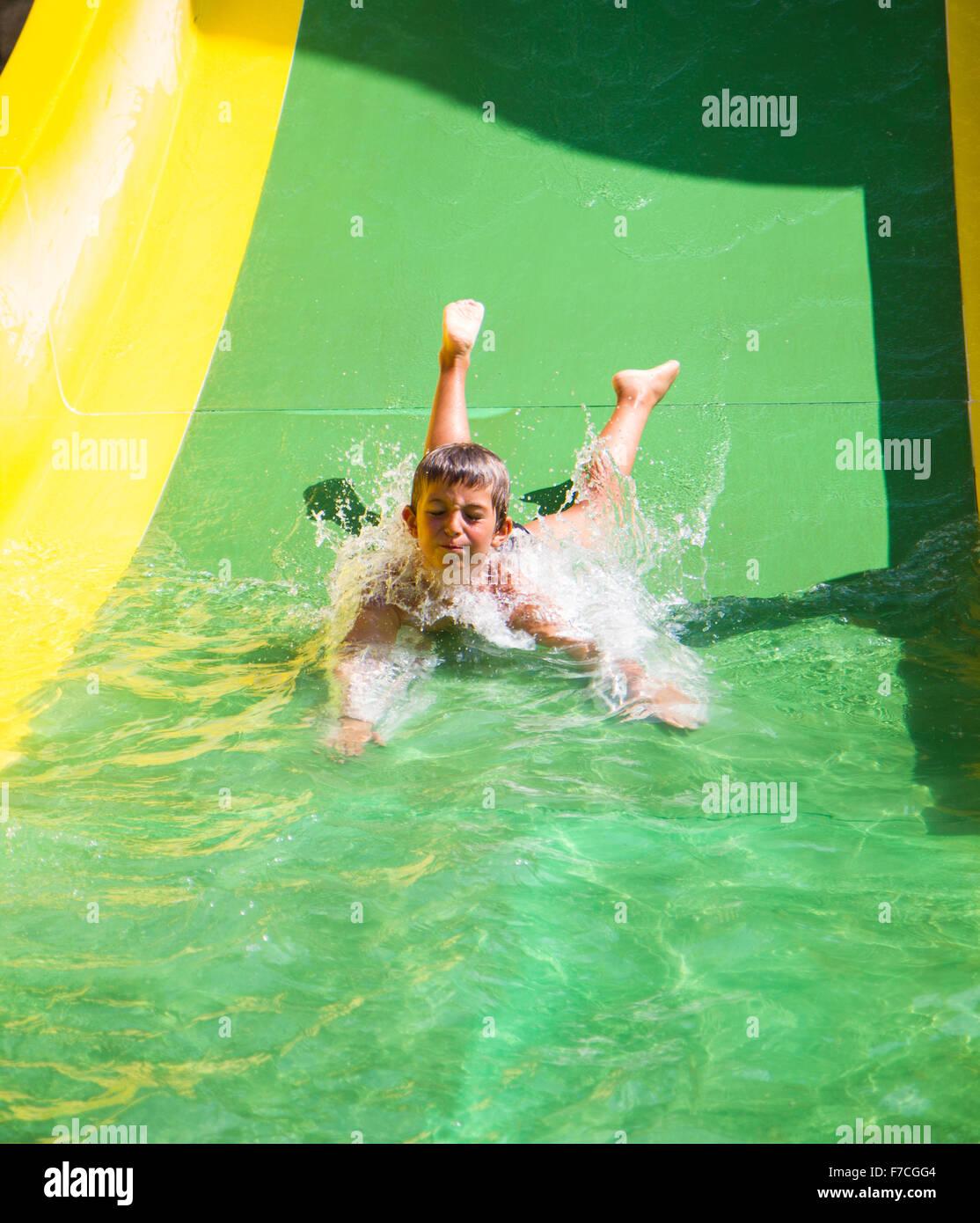 Enfant jouant sur l'eau glisser à amusement park Photo Stock