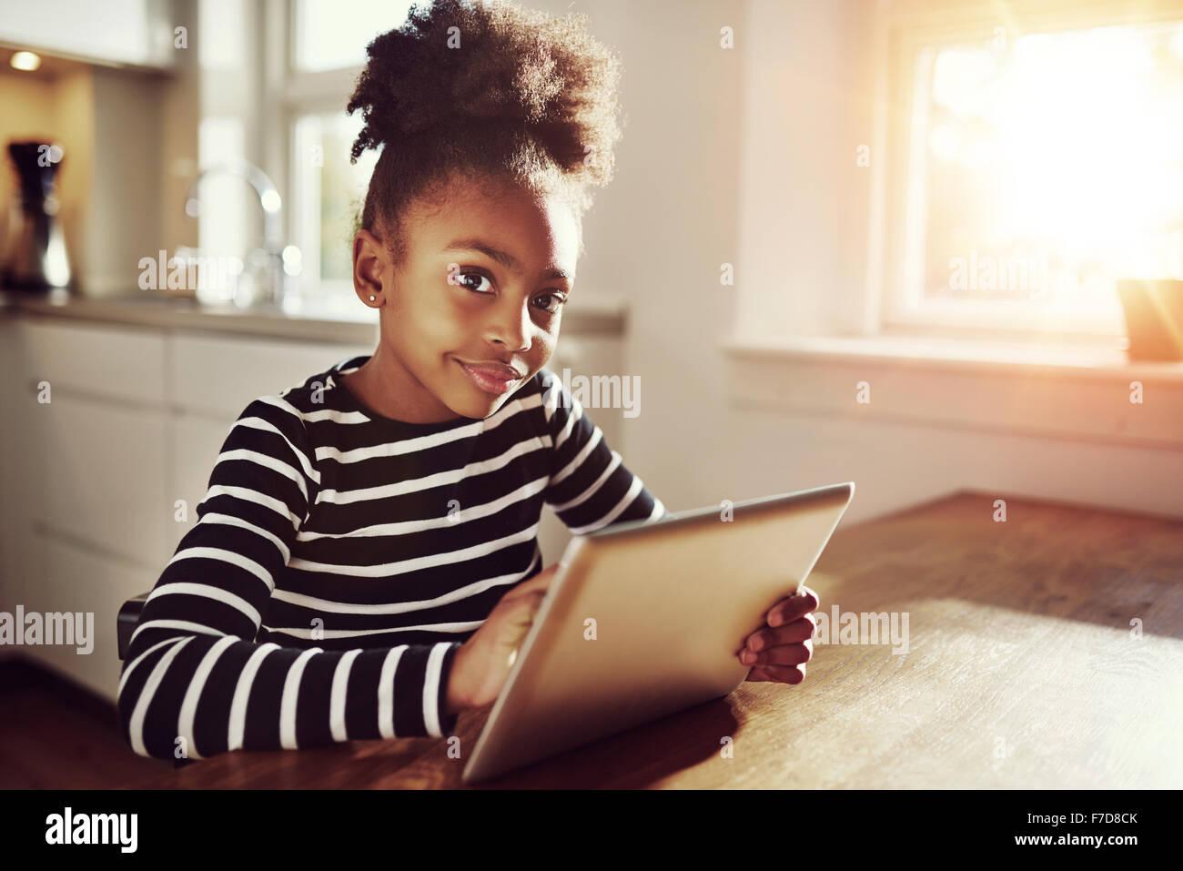 Young black girl assis regardant la caméra avec une expression pensive alors qu'elle navigue sur internet Photo Stock