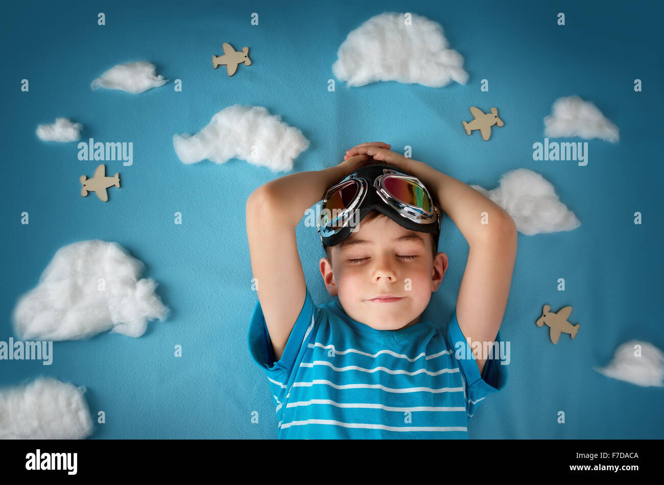 Boy lying on blanket with white clouds Photo Stock