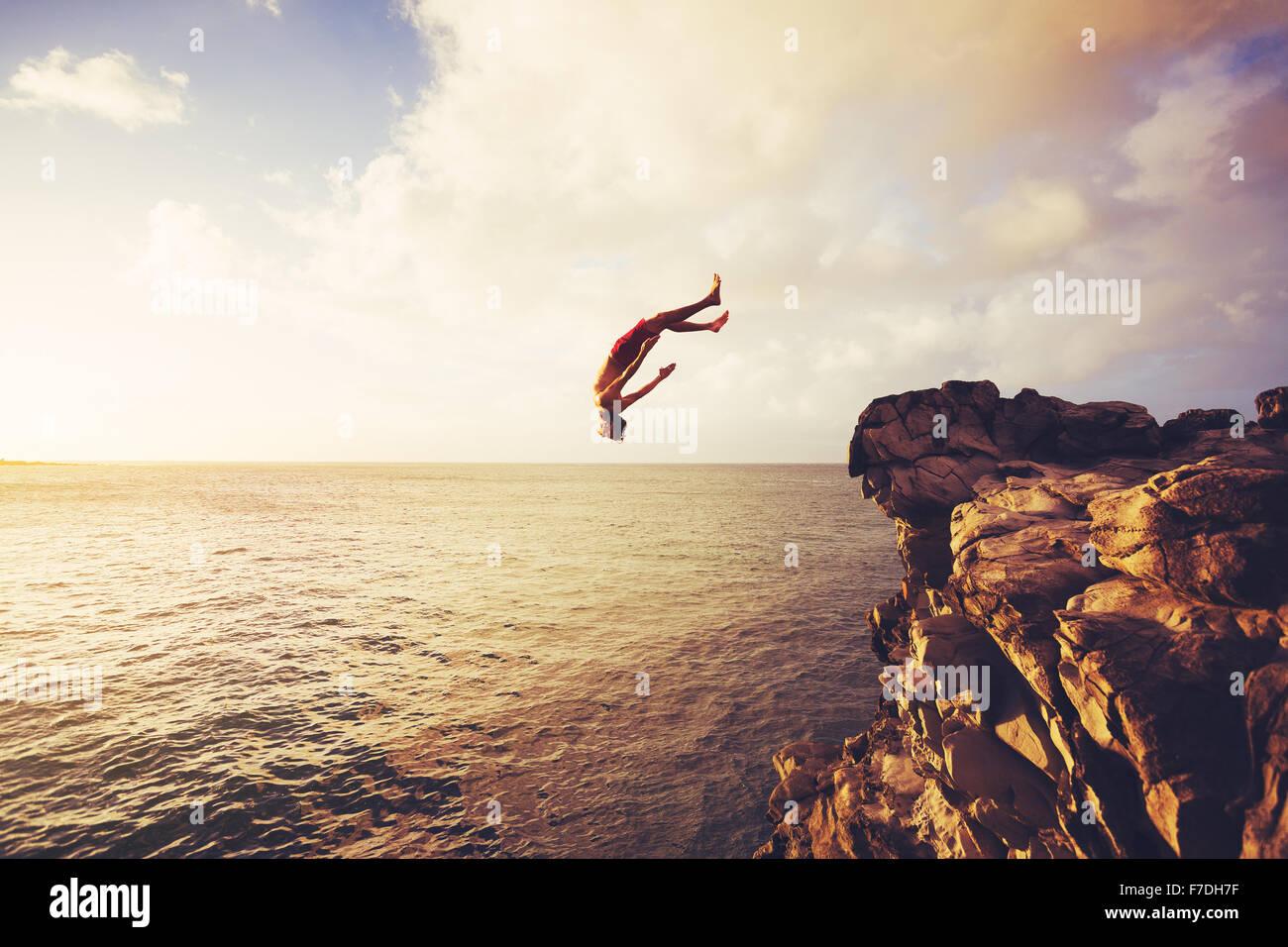 Saut de falaise dans l'océan au coucher du soleil d'été, Vie Photo Stock