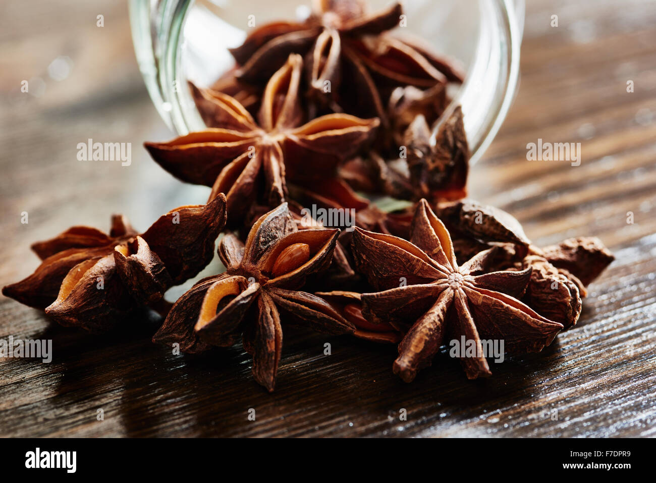 L'anis étoilé, le bocal en verre de table en bois sombre. Photo Stock