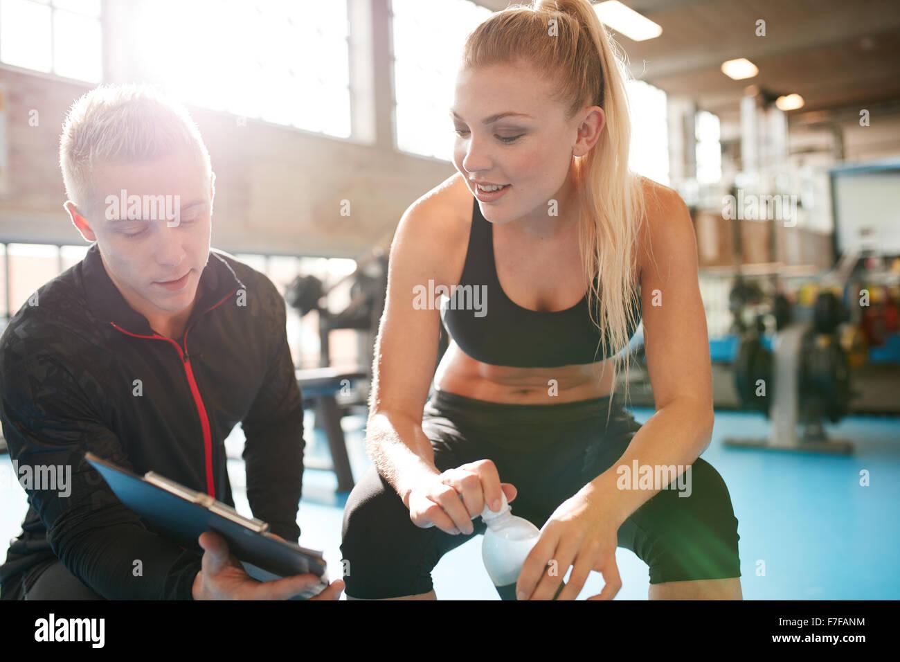 Vue d'un entraîneur personnel aider jeune femme avec son plan de remise en forme. Salle de fitness trainer Photo Stock