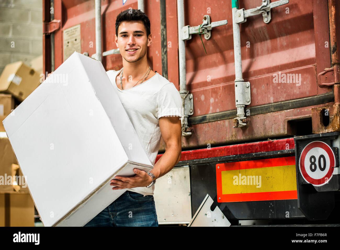Waist Up Portrait of Young Smiling Man Holding Large White boîte à côté de la voiture du train Photo Stock