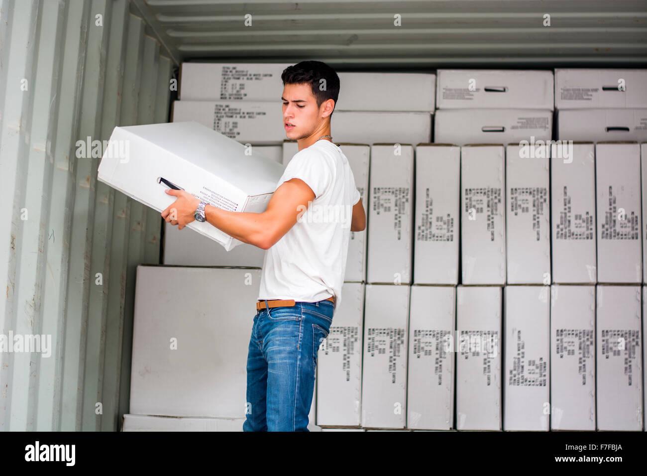 Waist Up Portrait of Young Smiling Man Holding Large White fort à côté de Freight Train Voiture  Photo Stock