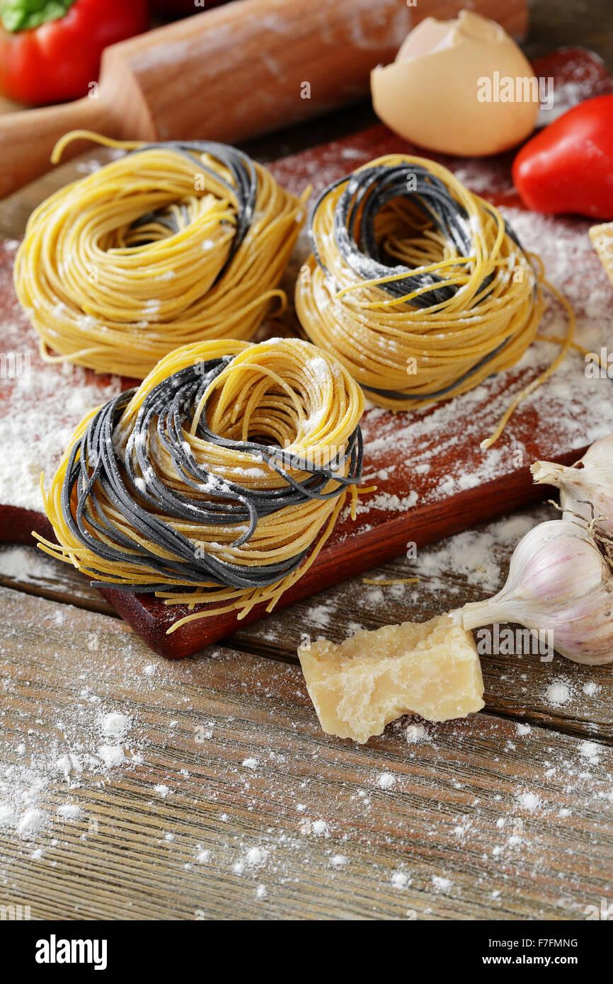 Pâtes alimentaires non cuites avec des ingrédients de cuisine, gros plan Photo Stock