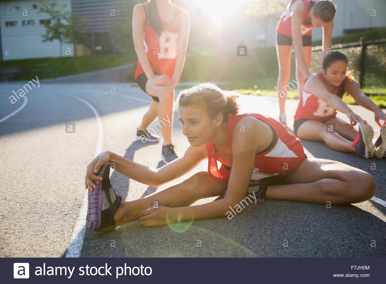 L'athlète de l'école secondaire s'étend de la jambe sur une piste de course Photo Stock