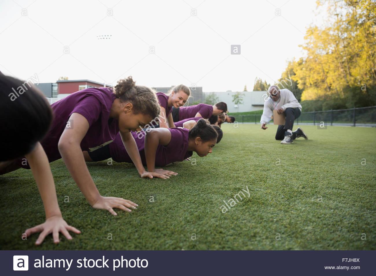 Professeur d'éducation physique d'encourager les élèves faisant push-ups Photo Stock