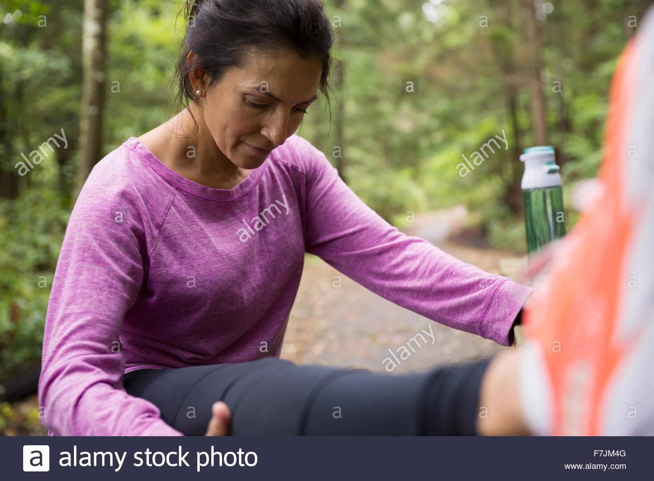Woman stretching leg préparation de l'exécution dans les bois Photo Stock