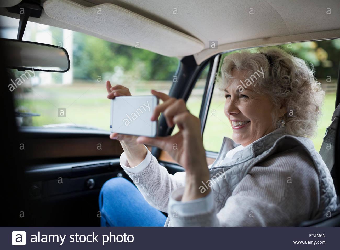 Senior woman using camera phone in car Photo Stock