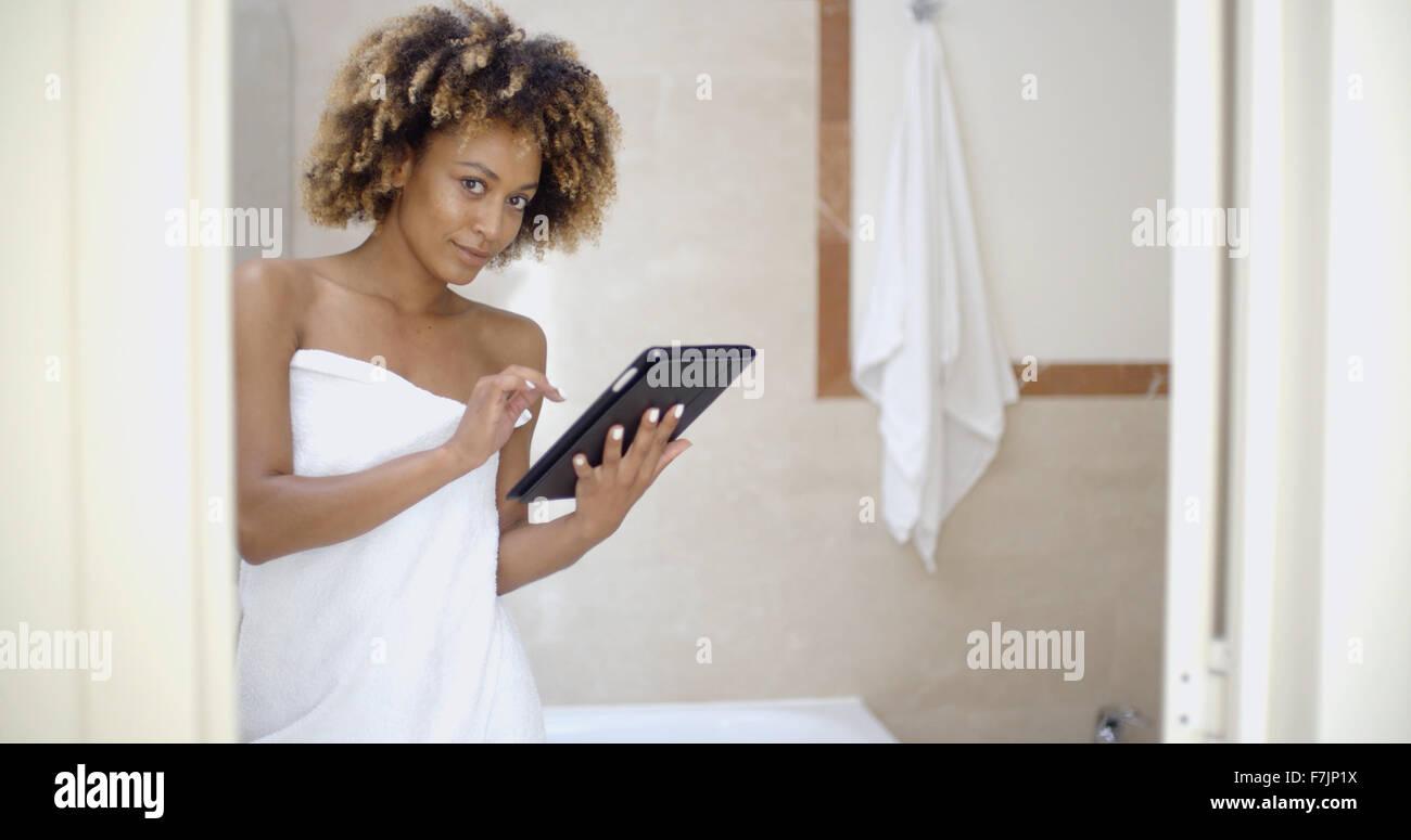 Fille Dans les serviettes de bain en utilisant le pavé tactile Photo Stock