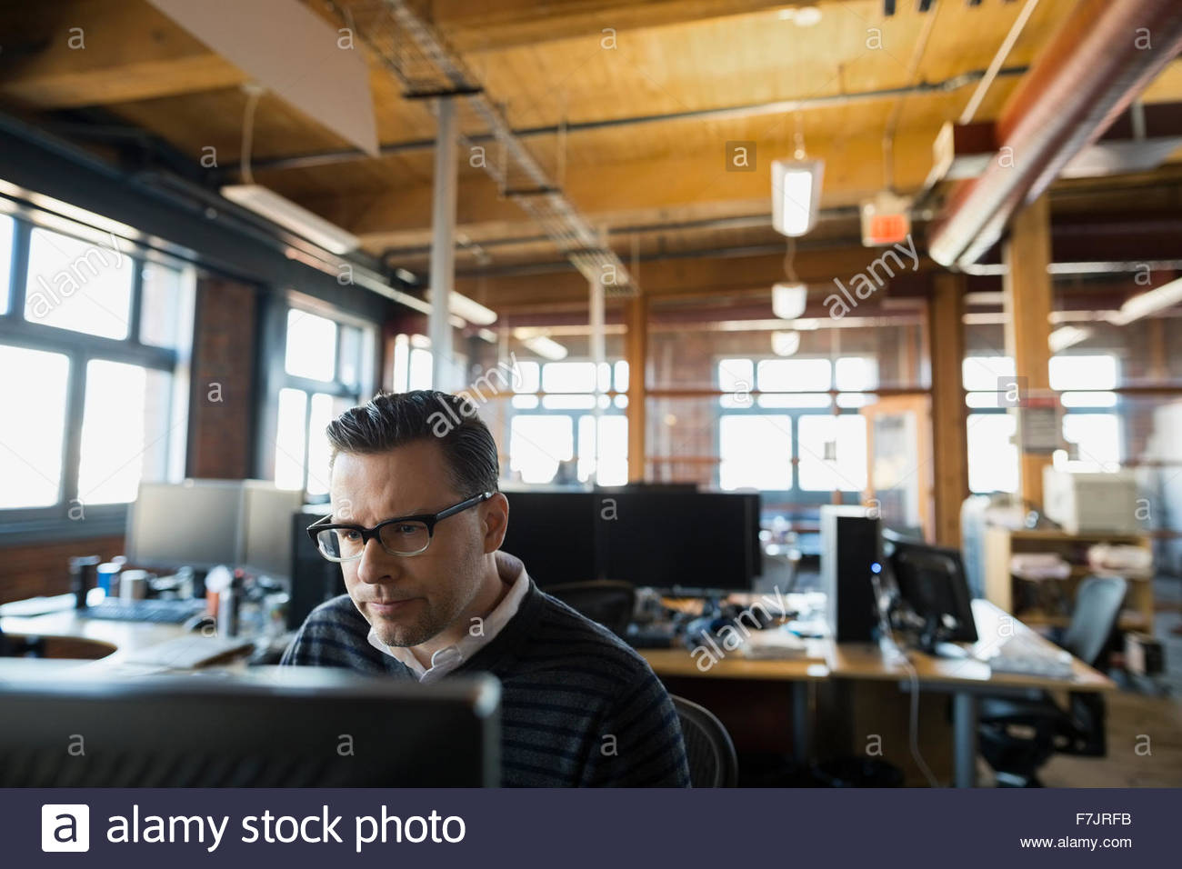 Serious businessman working at computer in office Photo Stock
