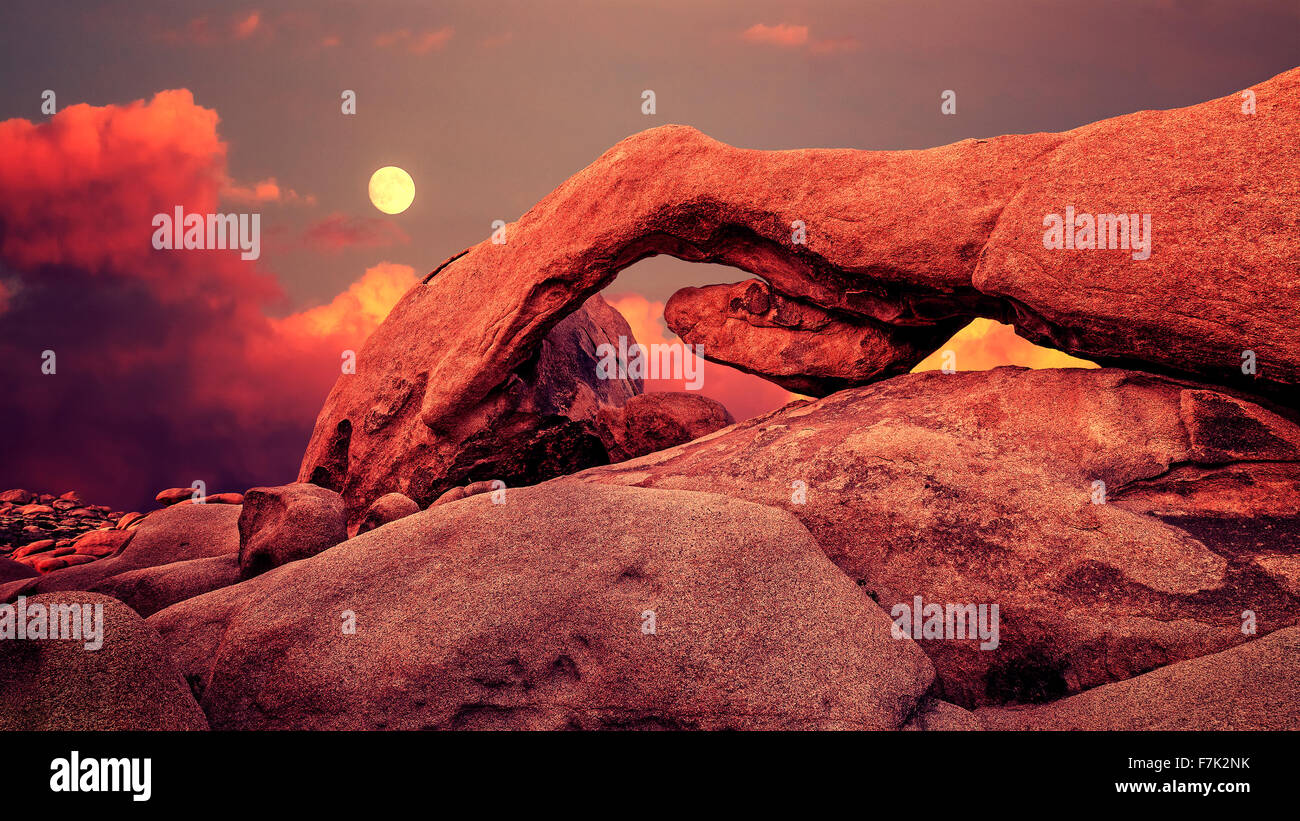 Coucher de soleil et lever de lune pourpre sur arch dans Joshua Tree National Park, Californie, USA. Photo Stock
