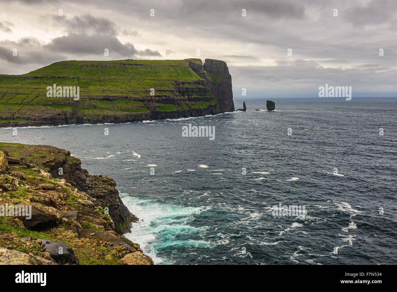 Giant Sea Cliff et piles de la mer peu après tempête des îles Féroé. Photo Stock