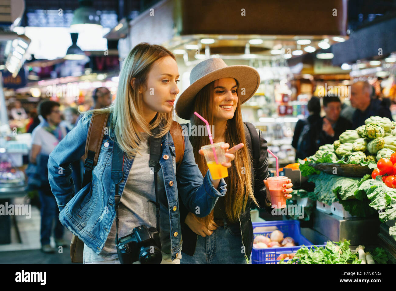 Deux jeunes femmes de boire des smoothies sur un marché Banque D'Images