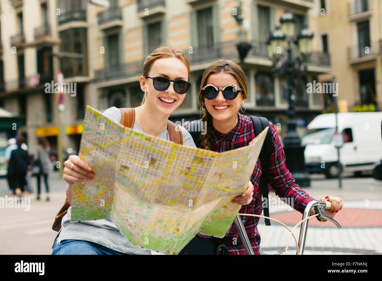 Espagne, Barcelone, deux jeunes femmes heureux avec la carte sur les bicyclettes dans la ville Banque D'Images
