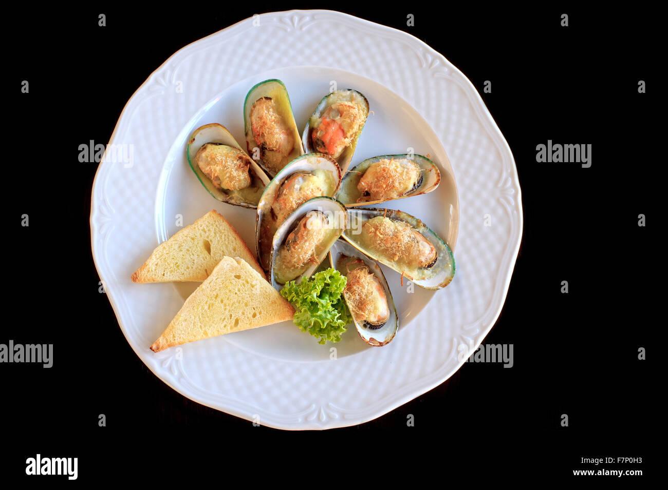 Grosses moules frites avec du fromage et du pain grillé en plaque blanche Banque D'Images