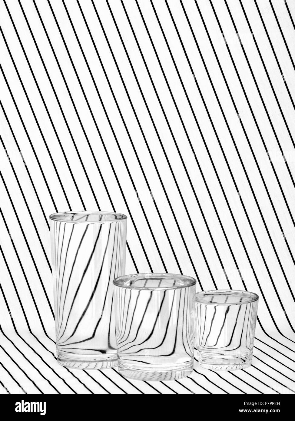 Trois verres sur tissu rayé, noir et blanc. La réfraction. Photo Stock