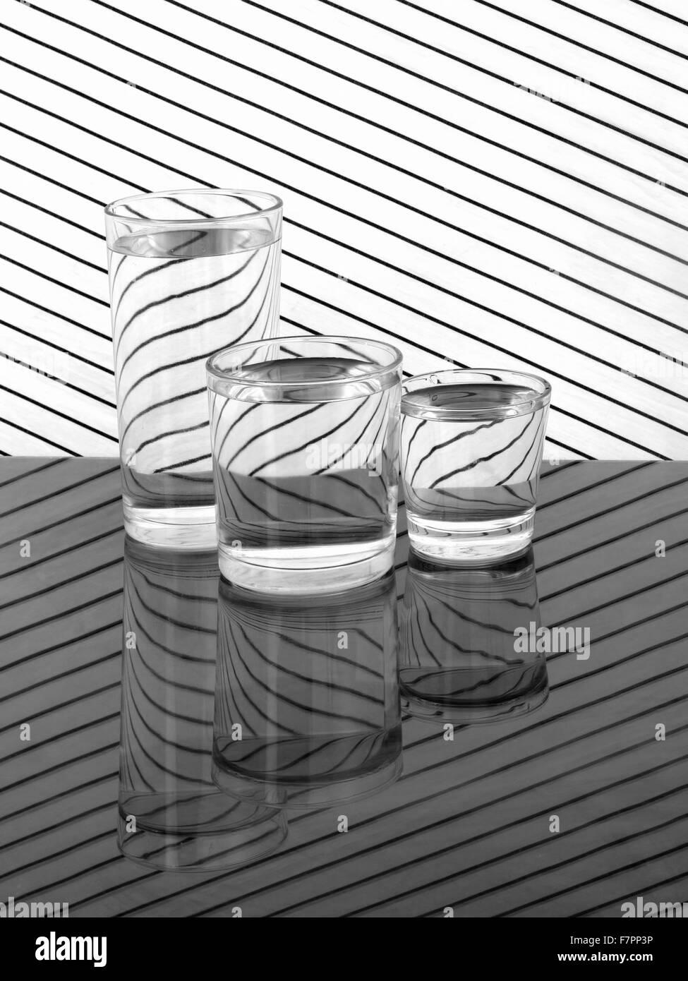 Verres d'eau sur un tissu à rayures - Réfraction et réflexion Photo Stock