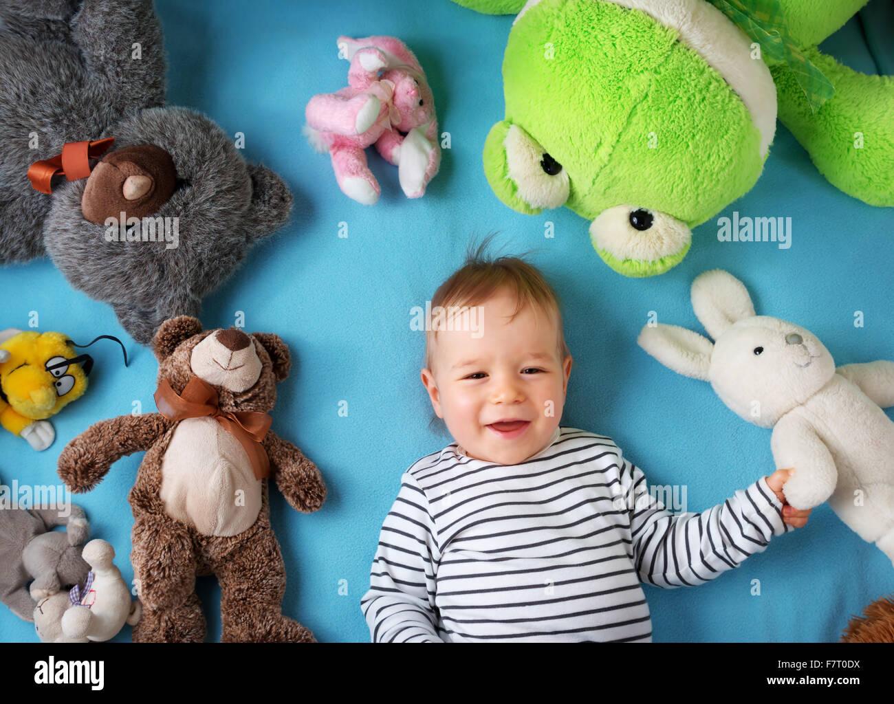 Heureux un an garçon couché avec de nombreux jouets en peluche Photo Stock