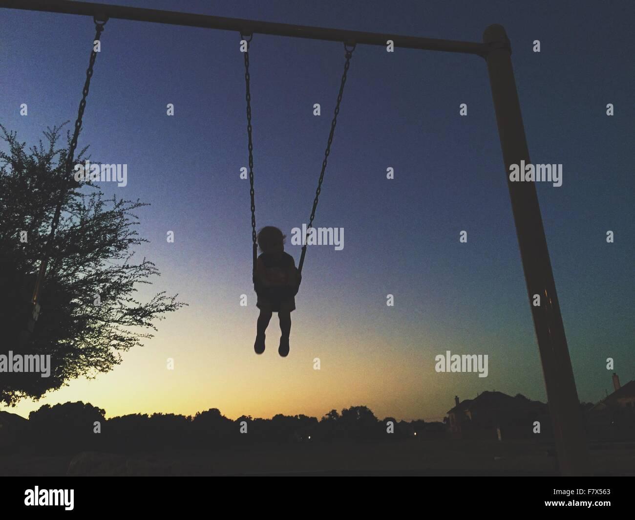 Silhouette d'un bambin sur swing dans le coucher du soleil Photo Stock