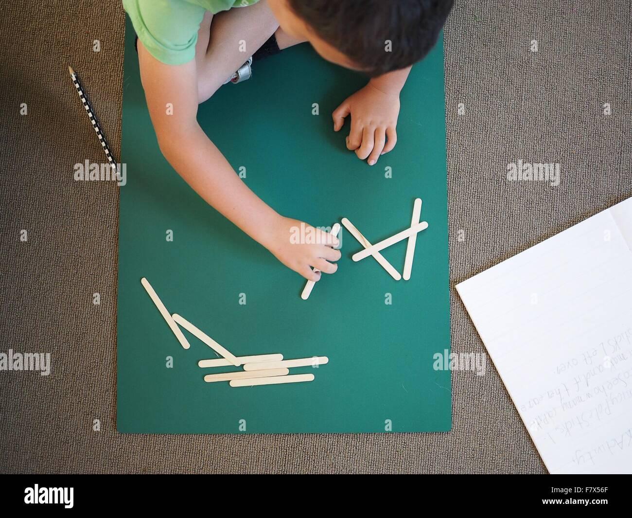 Garçon faisant l'école primaire mathématiques avec des bâtons Photo Stock