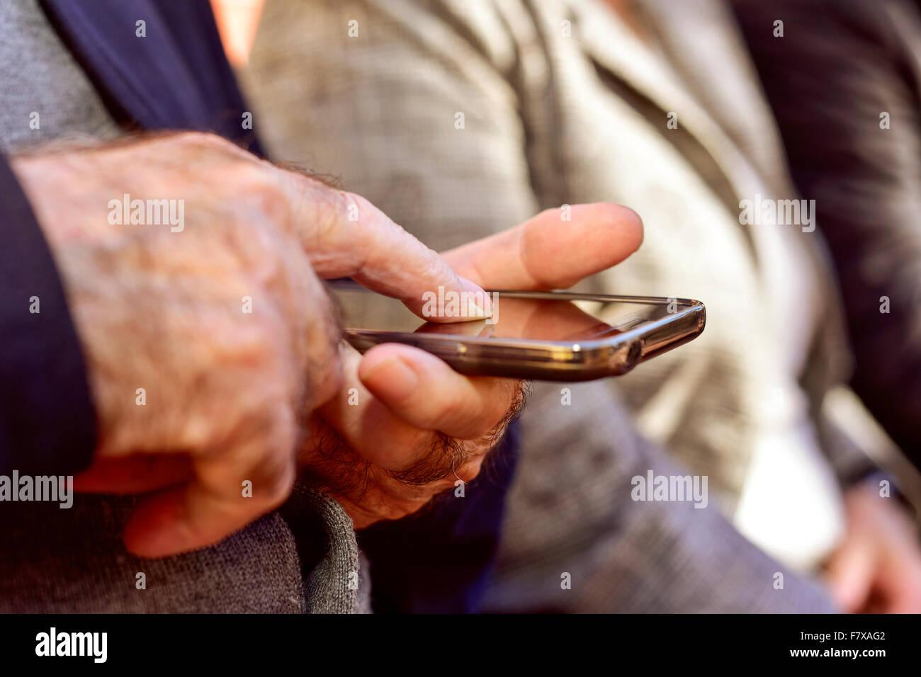 Libre d'un vieil homme de race blanche à l'aide d'un smartphone outdoors Photo Stock