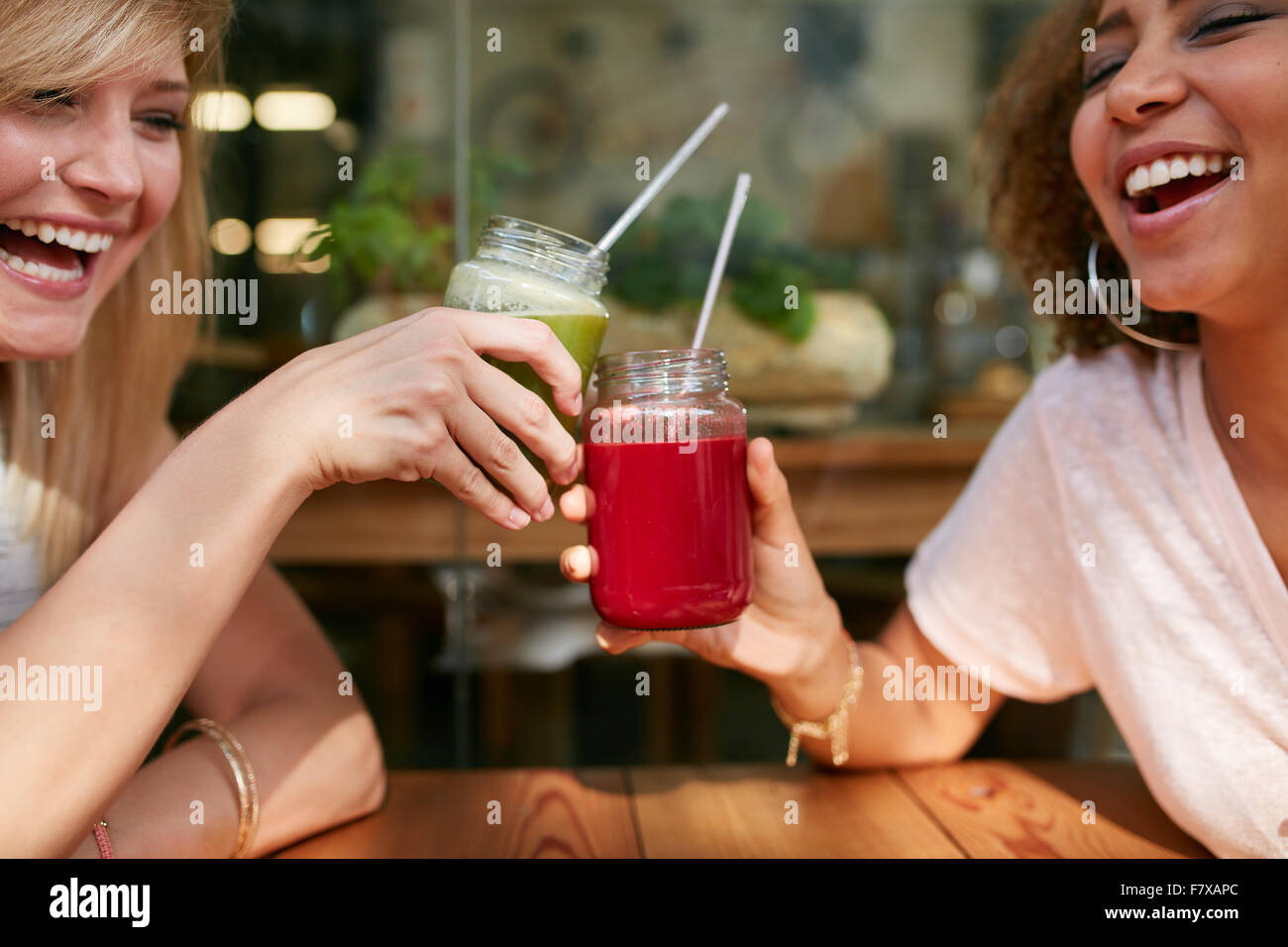 Close up shot of young friends toasting drinks at sidewalk cafe. Deux femmes heureux de prendre un verre et discuter Banque D'Images