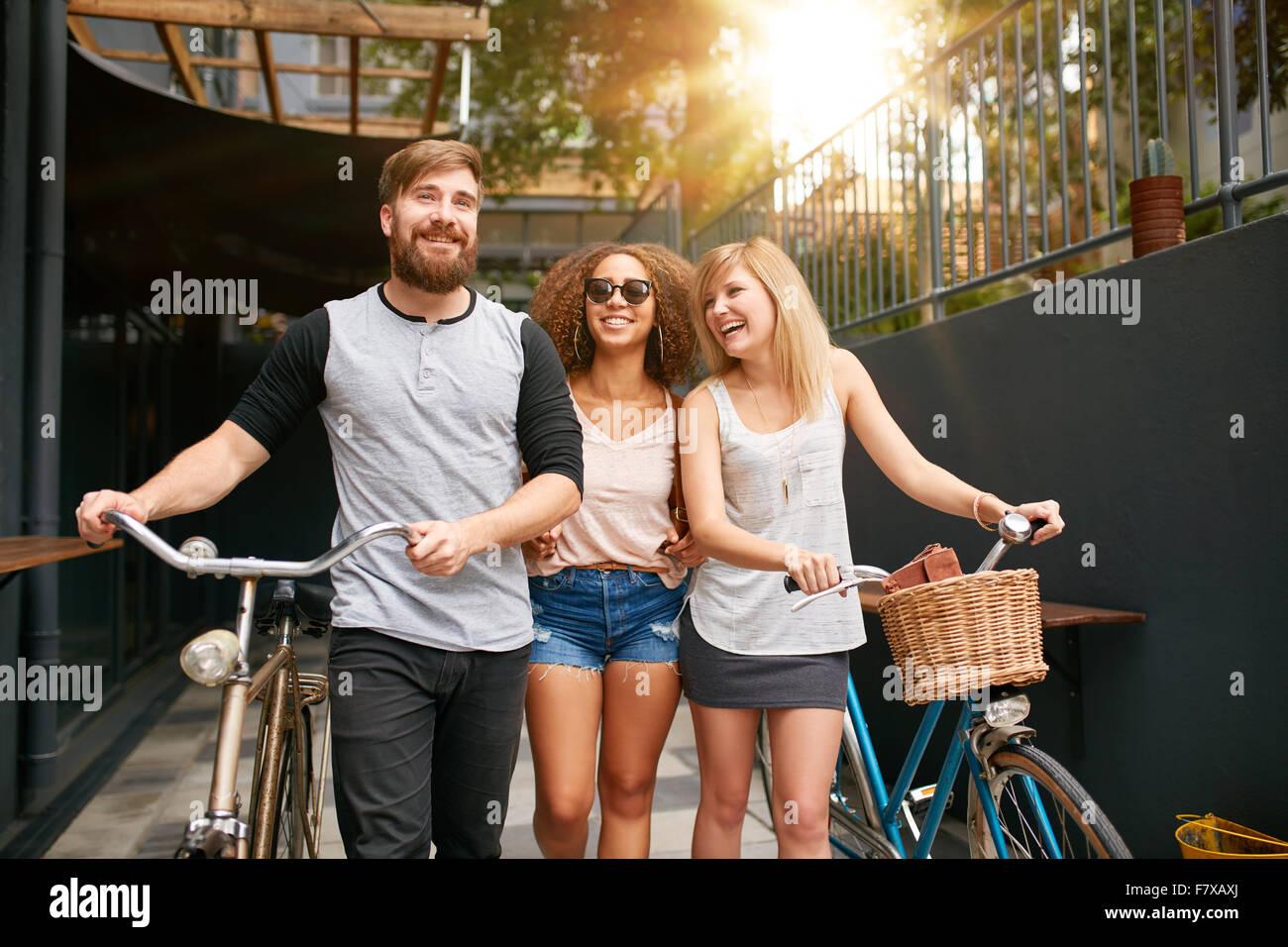 Trois jeunes gens marchant dans la rue avec leurs bicyclettes et d'avoir du plaisir. Les amis masculins et féminins Photo Stock