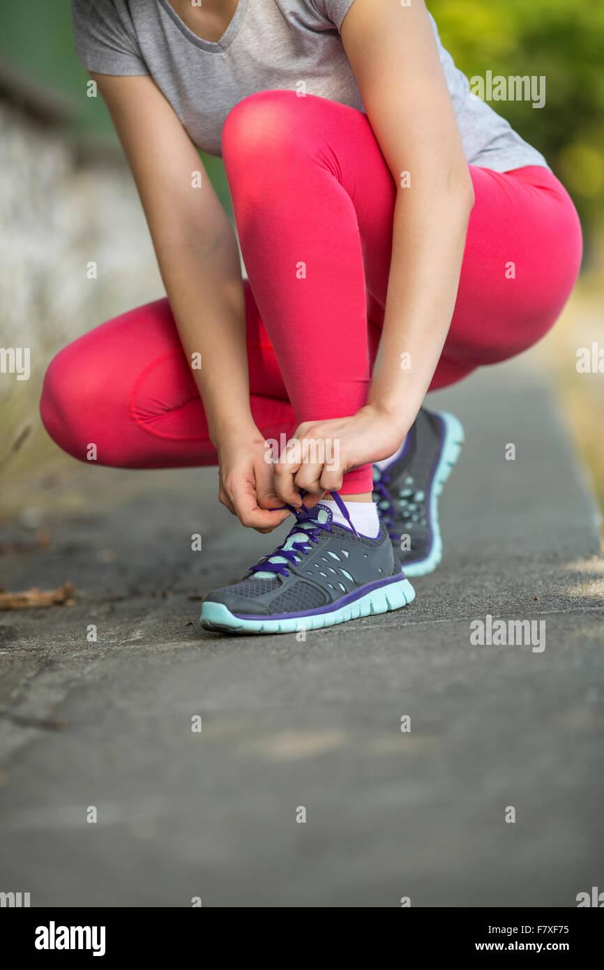 Libre de jeune fille sportive attacher ses lacets de sneakers à l'extérieur. Photo Stock
