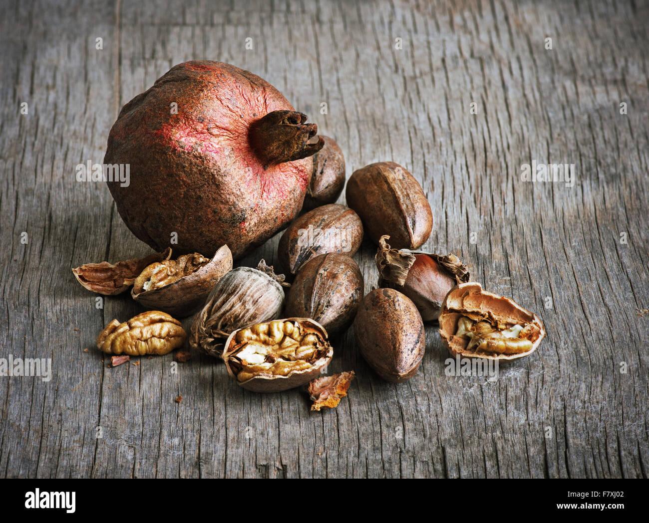 Grenade et noix de pécan sur une table en bois Photo Stock