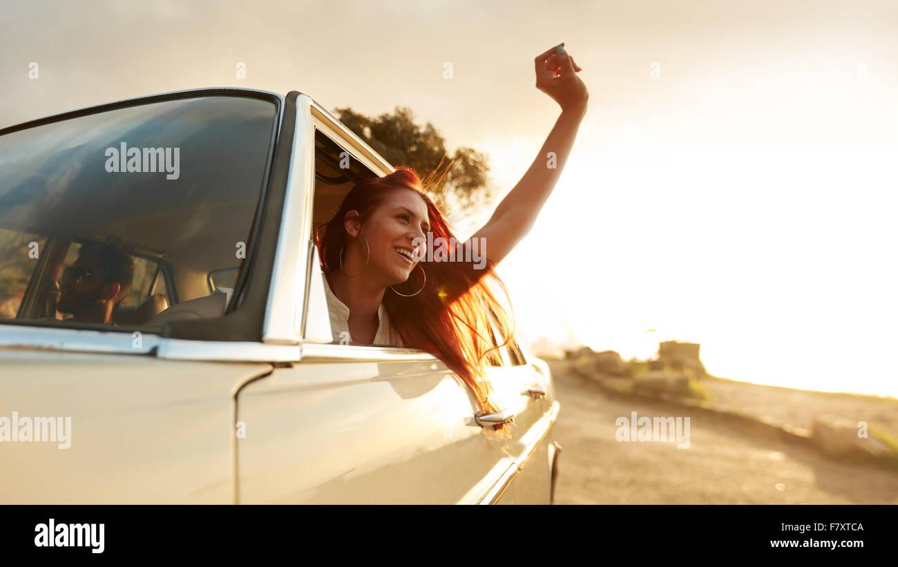 Tourné de belle jeune femme profitant de road trip sur une journée d'été. Les jeunes femmes excitées levant la main hors de la voiture. Banque D'Images