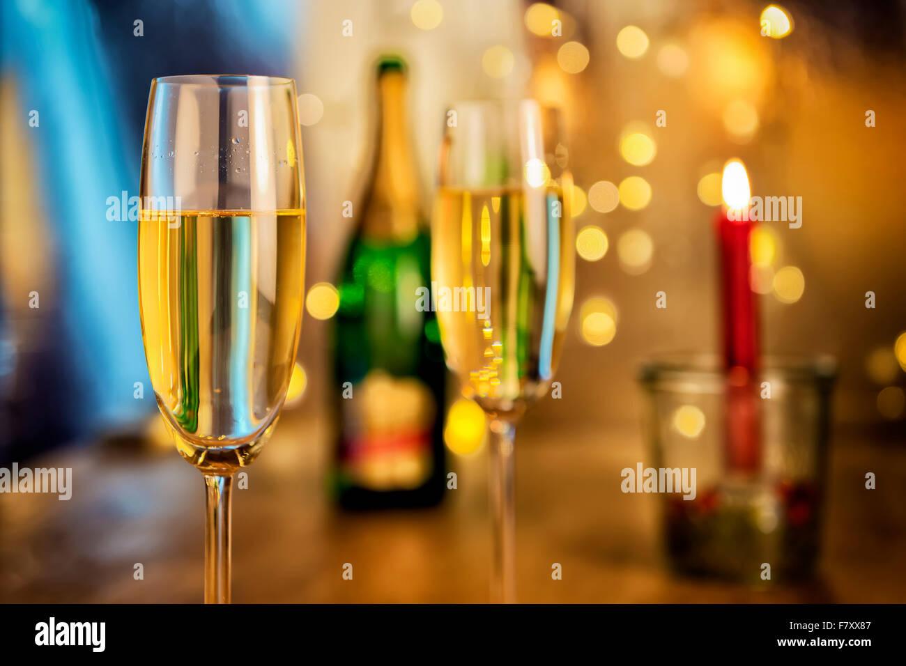 Image de deux verres de champagne avec bouteille, bougie et feux de flou en arrière-plan Photo Stock