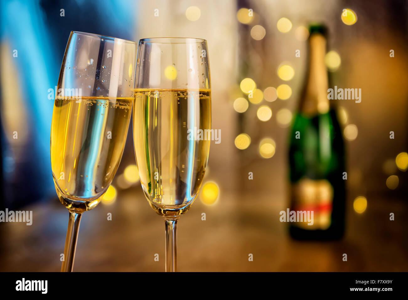 Image de deux verres de champagne avec bouteille et feux de flou en arrière-plan Photo Stock