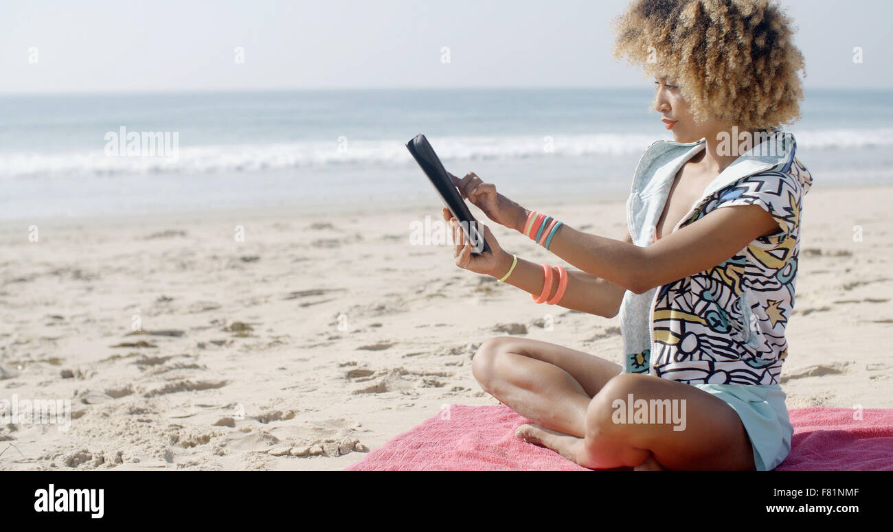 Femme utilise tablette tactile sur la plage Photo Stock