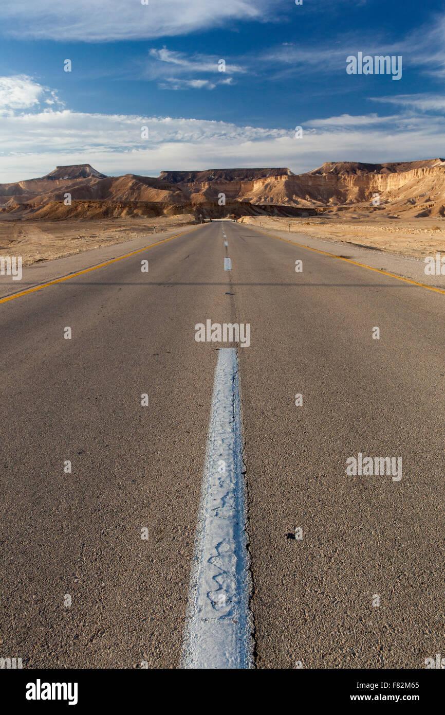 Une route qui s'étend en dehors de l'horizon dans le désert du Néguev israélien Photo Stock