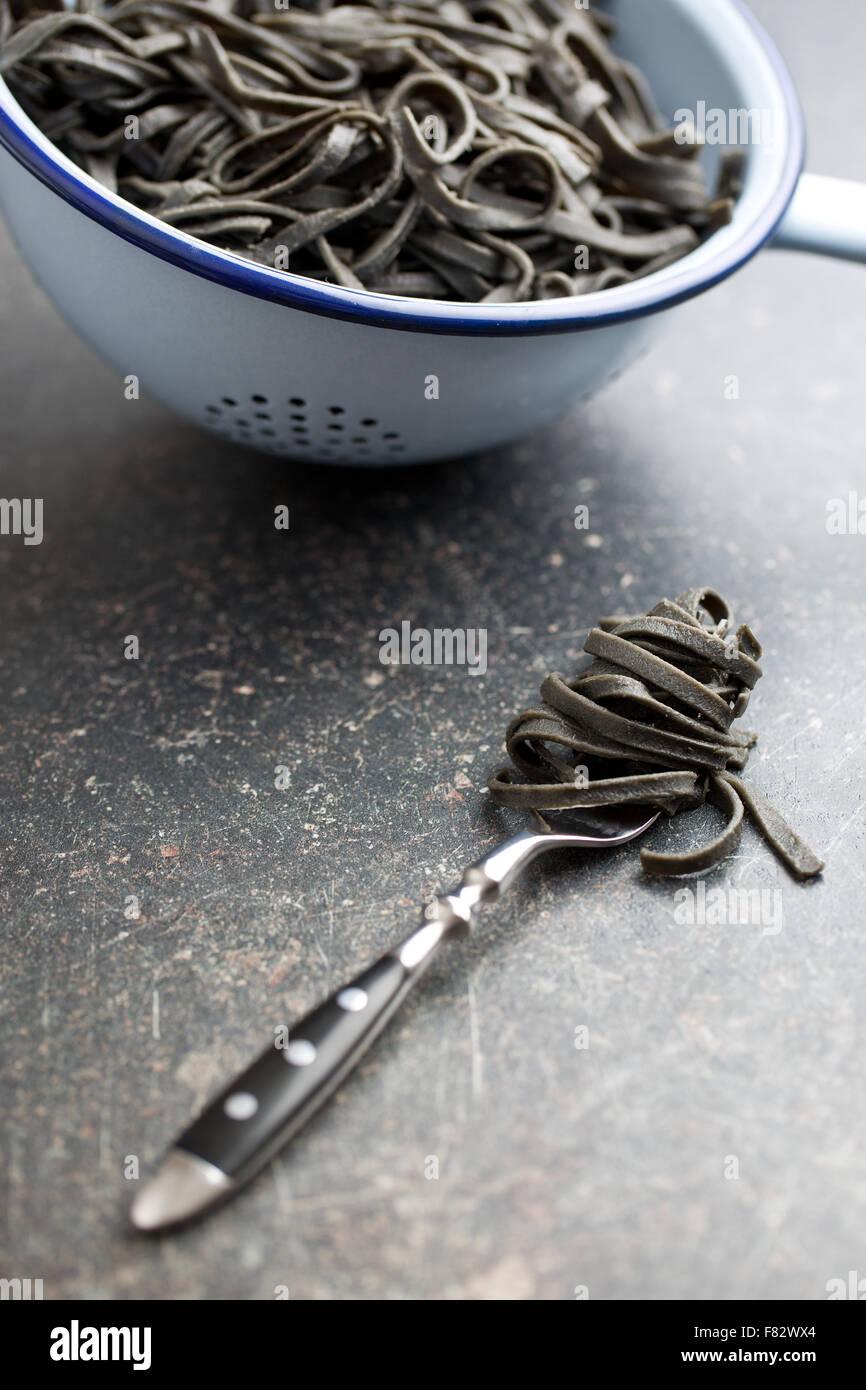 Noir avec des nouilles cuites squid encre sépia sur fourche Photo Stock