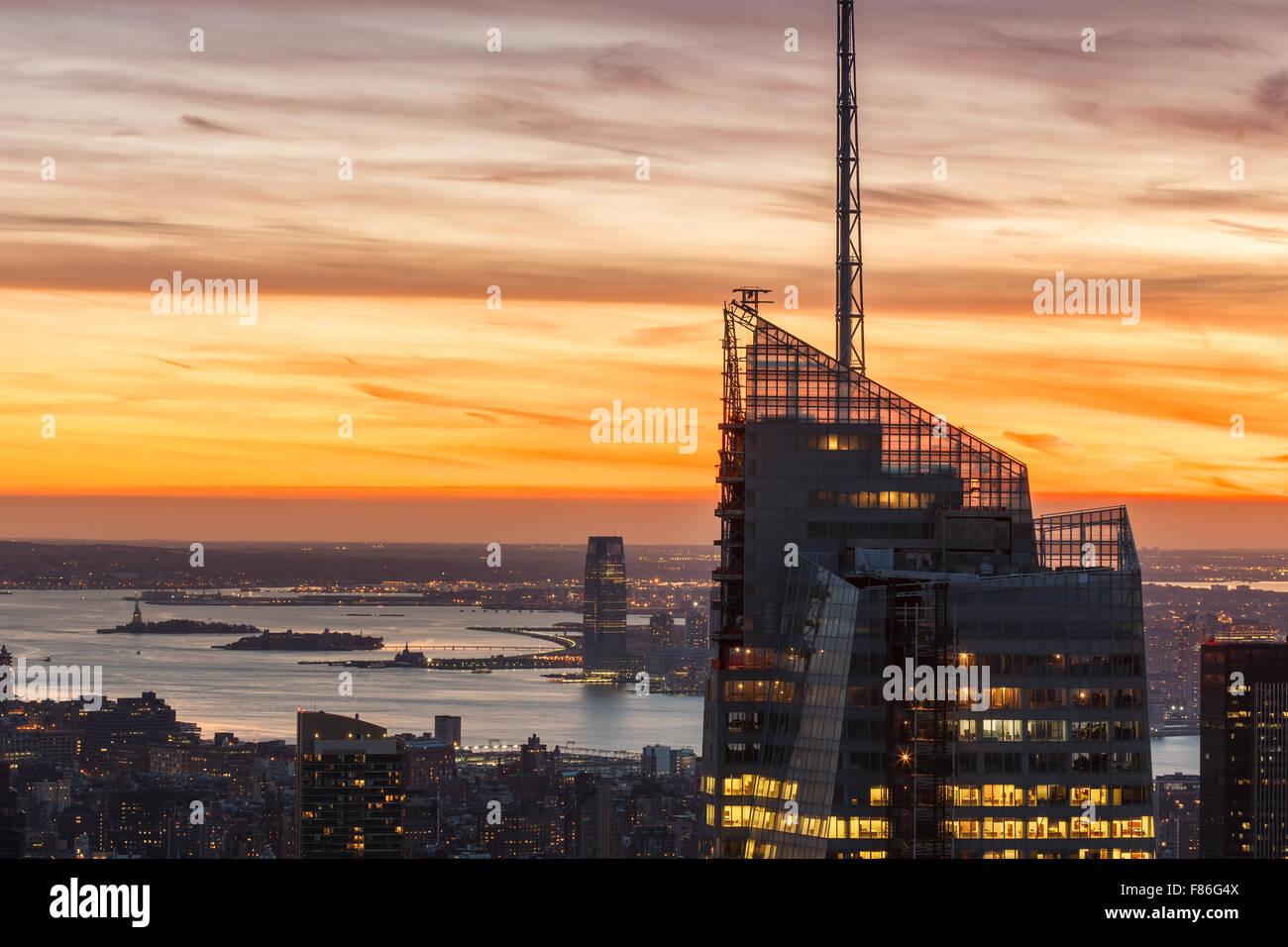 Vue aérienne de Manhattan et Bank of America Tower au coucher du soleil. La Statue de la liberté apparaît Photo Stock