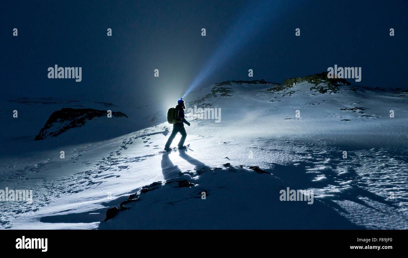 Randonneur en raquettes de nuit avec lampe frontale, l'islande Photo Stock