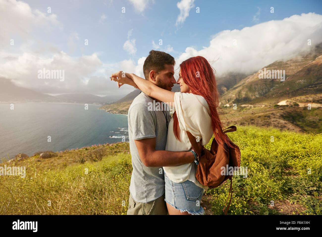 Vue latérale du couple en vacances. L'homme et la femme enlacés à l'extérieur. Photo Stock