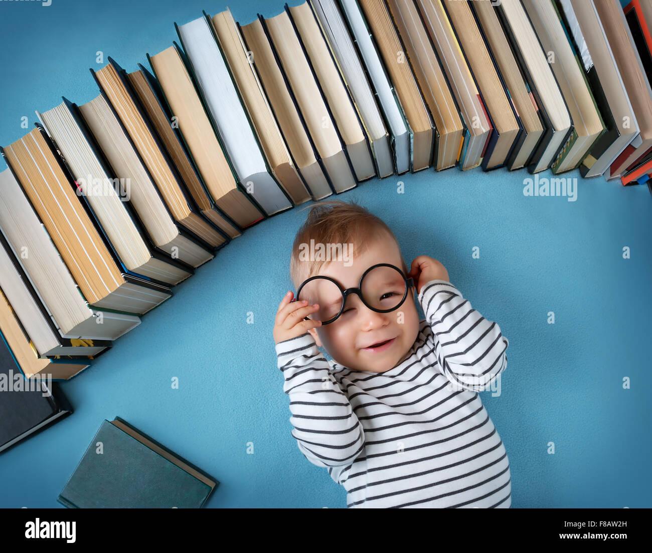 Un an bébé avec spectackles et livres Photo Stock