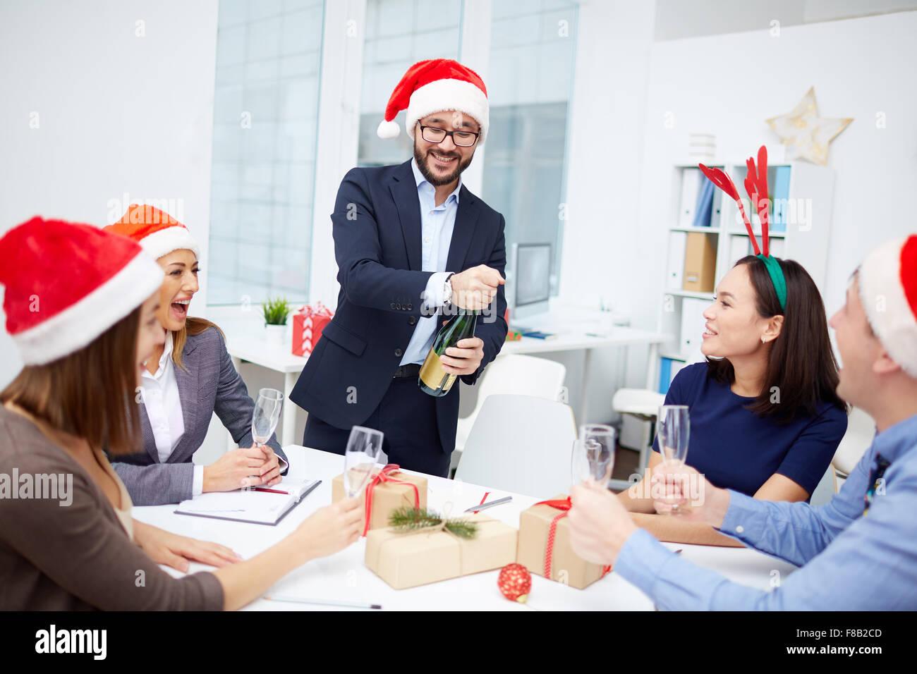 Groupe d'employés à leur collègue à l'ouverture de bouteille de champagne Photo Stock
